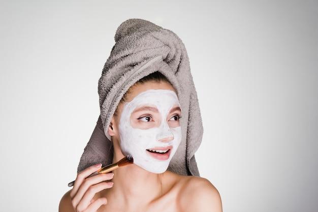 Jolie fille souriante avec une serviette sur la tête appliquant un masque nutritif blanc sur son visage avec un pinceau