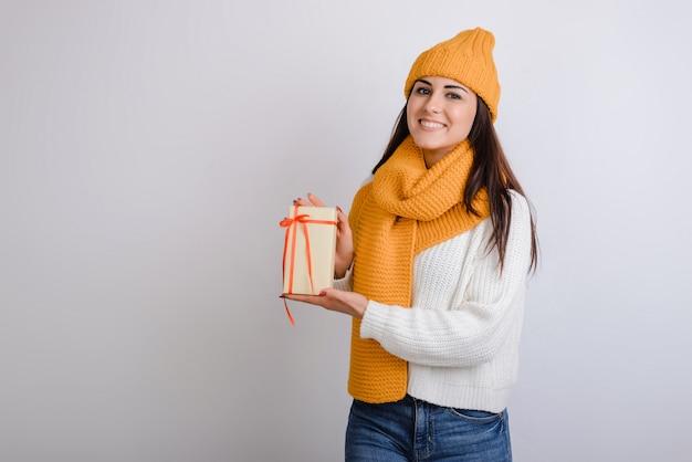 Jolie fille souriante tenant une boîte-cadeau et regardant la caméra sur fond gris