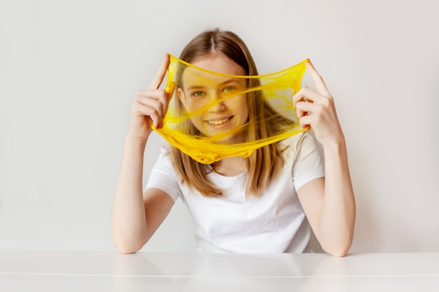 La jolie fille sourit et joue avec la boue jaune