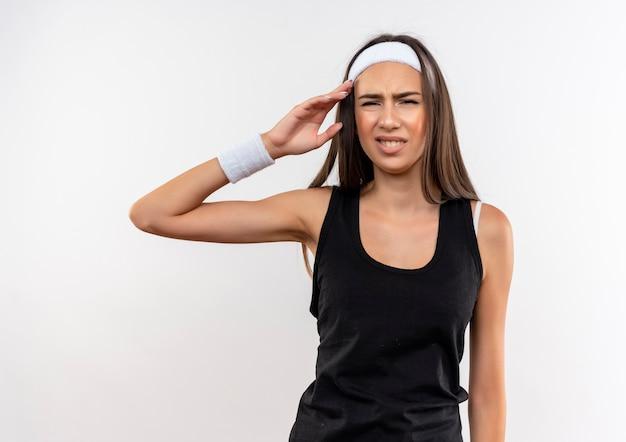 Jolie fille sportive agacée portant un bandeau et un bracelet mettant la main près de la tête isolée sur un mur blanc
