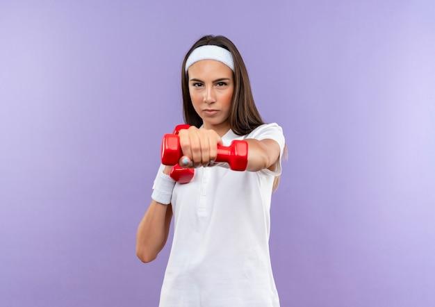 Jolie fille sportive confiante portant un bandeau et un bracelet d'eau potable isolée sur un mur violet