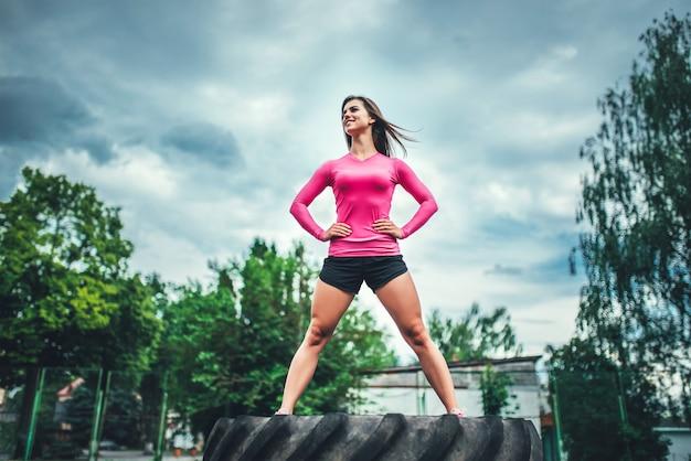Jolie fille sportive debout sur un énorme pneu en plein air