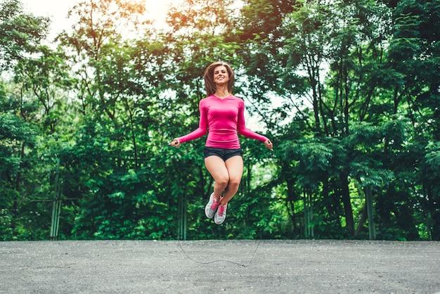 Jolie fille sportive avec une formation de corde en plein air