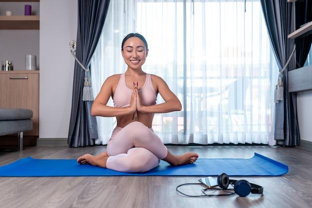 Jolie fille sportive souriante posant assis en tailleur et tenant ses mains jointes sur sa tête
