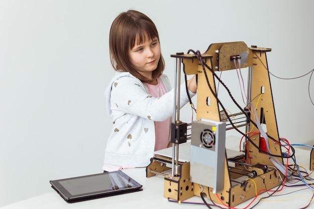 Jolie fille avec des stores d'obturation imprimés en 3d regarde son imprimante 3d pendant qu'elle imprime son modèle 3d.