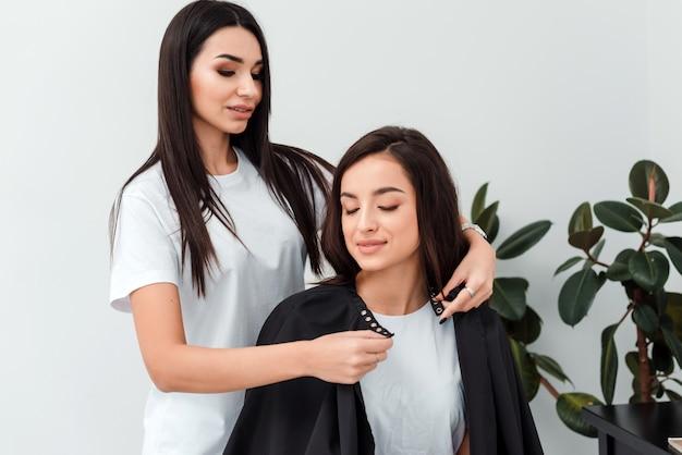 Jolie fille styliste habille client coiffure peignoir