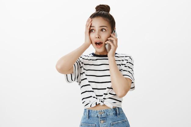 Jolie fille surprise et soulagée recevoir de bonnes nouvelles par appel téléphonique, parler sur smartphone