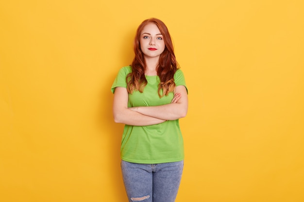 Jolie fille en t-shirt vert décontracté et debout, les bras croisés sur fond jaune, étant sérieuse, regardant la caméra, a les cheveux ondulés rouges et les lèvres brillantes.