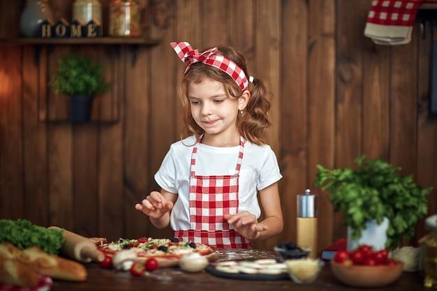 Jolie fille en tablier à damier cuisson pizza