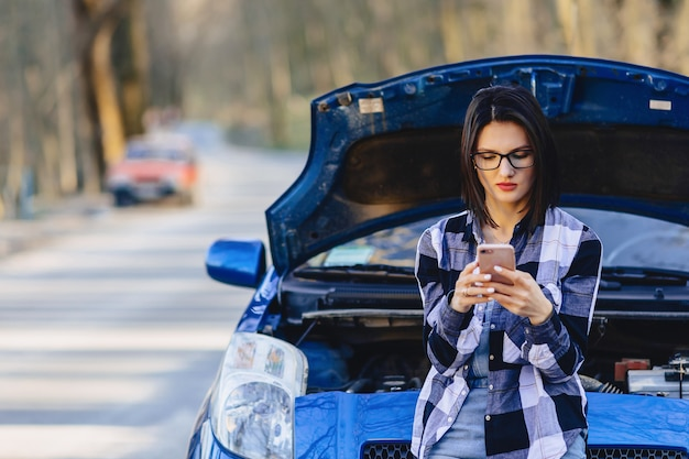 Jolie fille avec téléphone près du capot ouvert de la voiture