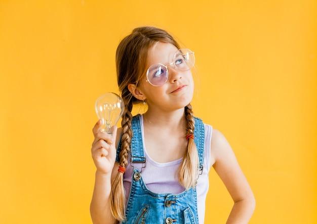Jolie fille tenant une ampoule pointant son doigt dessus sur fond jaune