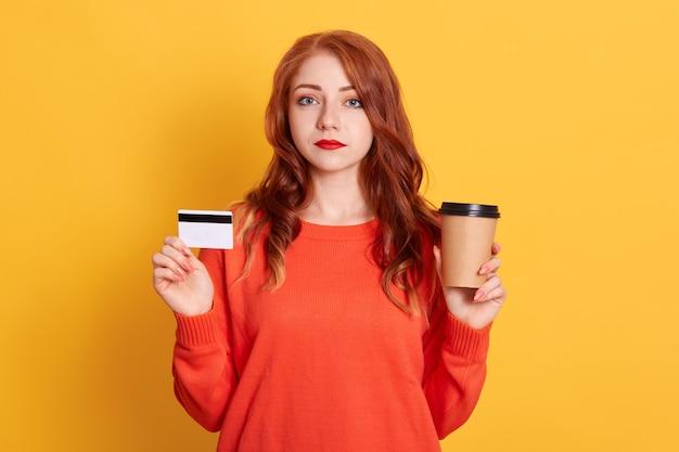Jolie fille tenant une carte blanche et une tasse de café jetable, a un regard sérieux