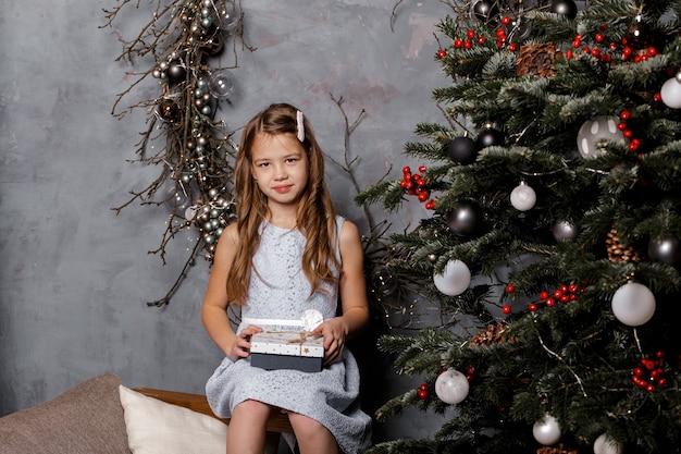 Jolie fille tenant des coffrets cadeaux de noël et souriant devant l'arbre de noël
