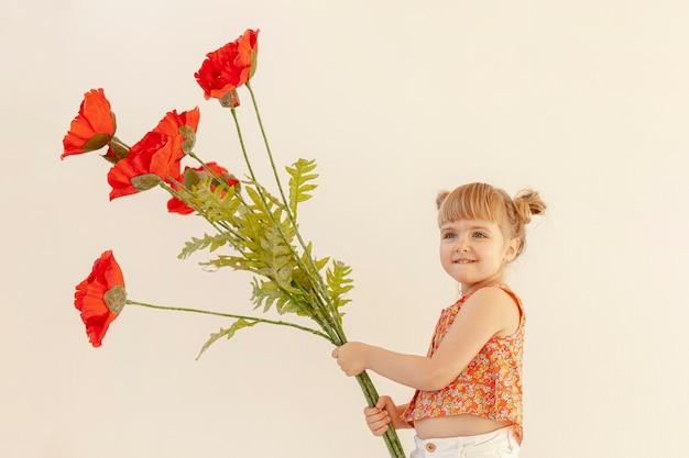 Jolie fille tenant de grandes fleurs