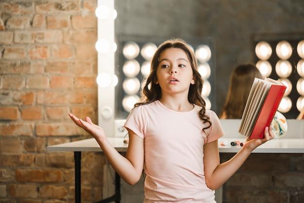 Jolie fille tenant un livre à répéter dans les coulisses