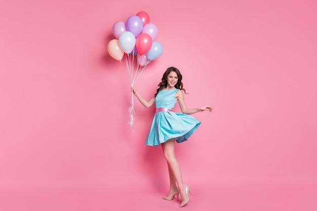 Jolie fille tenant à la main des boules d'hélium en bouquet isolés sur fond de couleur pastel rose
