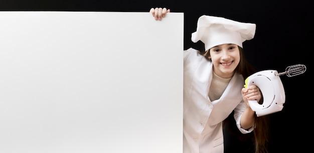 Jolie fille tenant un mélangeur électrique