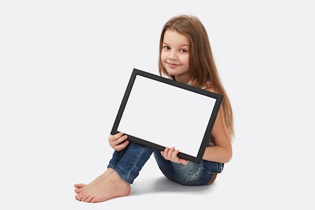 Jolie fille tenant une pancarte blanche