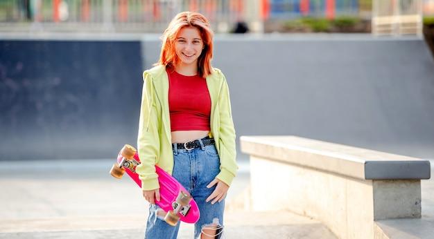 Jolie fille tenant une planche à roulettes et souriant à l'extérieur. patineuse près de la rampe d'équitation du parc en été