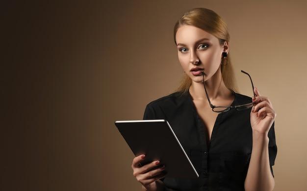 Jolie fille tenant la tablette et les verres et la pensée sur le mur brun - concept technologique fille tenant la tablette et la pensée