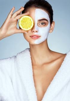 Jolie fille tenant une tranche de citron devant son visage et souriant
