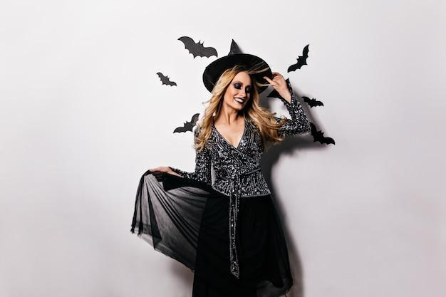 Jolie fille en tenue de carnaval souriant. sorcière blonde raffinée célébrant l'halloween.