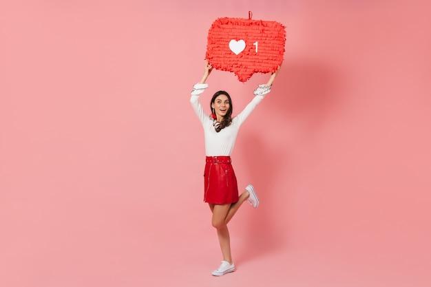 Jolie fille en tenue lumineuse souriante et démontrant joyeusement comme du réseau social sur fond rose.