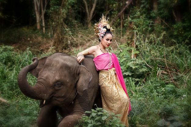 Jolie fille thaïlandaise en costumes traditionnels thaïlandais avec éléphant