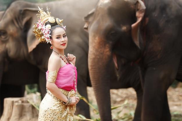 Jolie fille thaïlandaise en costumes traditionnels thaïlandais avec des éléphants