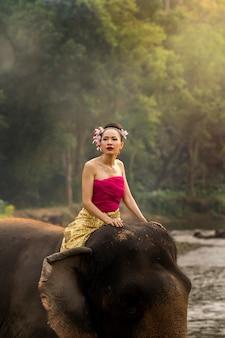Jolie fille thaïlandaise en robe thaïlandaise traditionnelle à dos d'éléphant