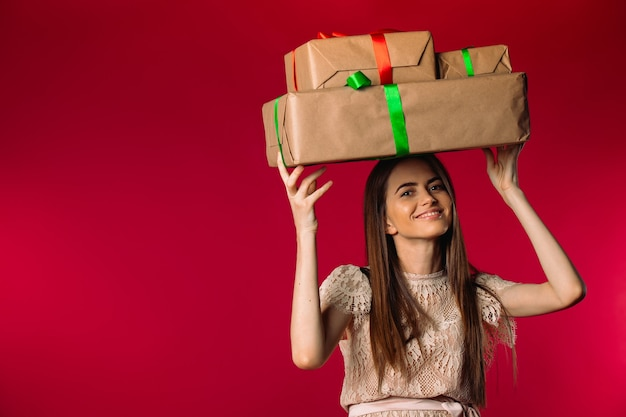 Jolie fille tient des cadeaux sur la tête et smileson fond rouge avec un espace vide