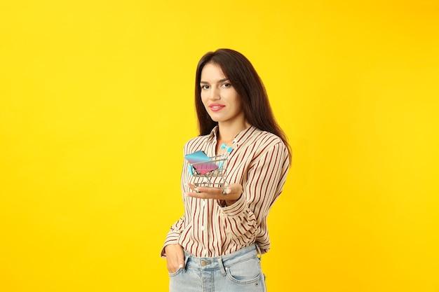 Jolie fille tient un chariot de magasin avec des cartes de crédit sur fond jaune.