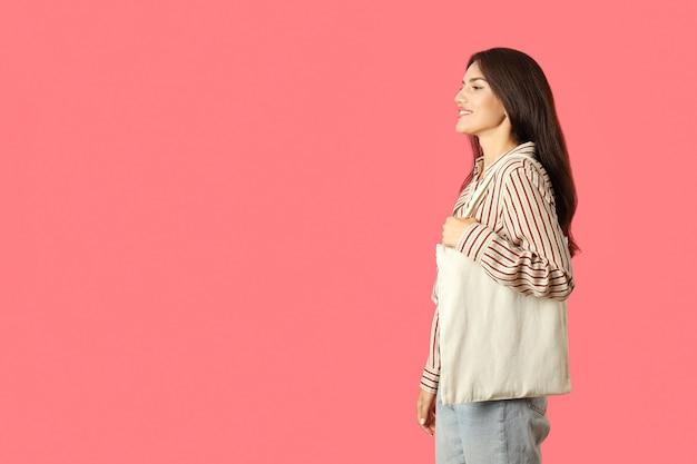 Jolie fille tient un sac en coton sur fond rose, espace pour le texte.