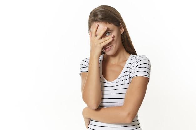 Jolie fille timide qui vous regarde à travers les doigts. jolie jeune femme européenne en t-shirt rayé posant en pose fermée, tenant la main sur son visage et regardant timidement avec un sourire charmant