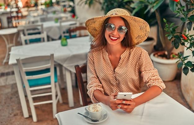 Jolie fille touriste dans des lunettes de soleil, un chemisier et un chapeau de paille boit du café dans un café de rue et utilise un smartphone. le concept de tourisme, voyage, loisirs.