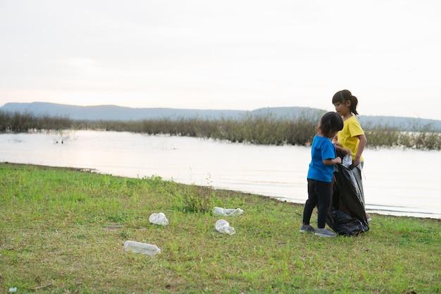 Jolie fille tout en aidant son frère à nettoyer les ordures
