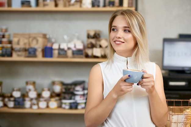 Jolie fille en train de boire du café en magasin, regardant de côté.