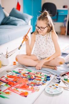 Jolie fille en train de peindre à la gouache au sol