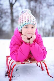 Jolie fille avec un traîneau dans un parc enneigé en vacances d'hiver