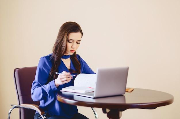 Jolie fille travaille pour un ordinateur portable