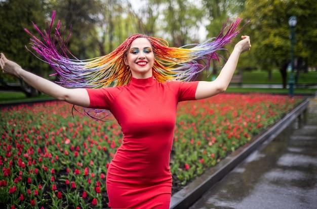 Jolie fille avec des tresses africaines multicolores et un maquillage expressif brillant dans une robe rouge moulante tourne dans le parc en profitant de l'arrivée du printemps