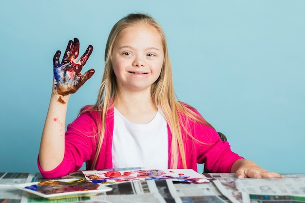 Jolie fille trisomique jouant avec des peintures