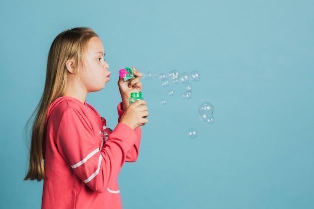 Jolie fille trisomique soufflant des bulles