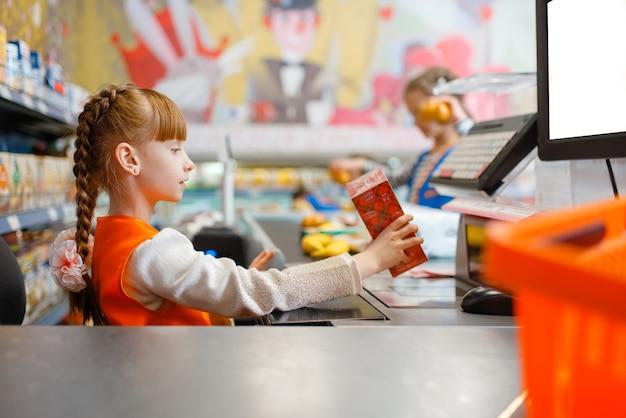 Jolie fille en uniforme à la caisse enregistreuse jouant vendeuse