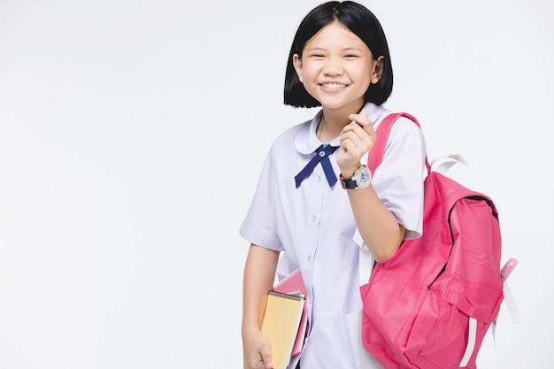 Jolie fille en uniforme d'étudiant avec papeterie sur gris