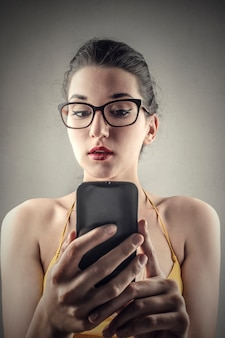 Jolie fille en utilisant une application sur son téléphone