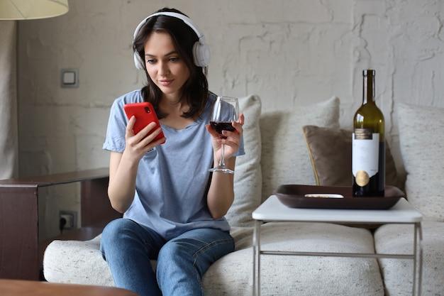 Jolie fille utilisant son smartphone sur un canapé à la maison dans le salon. écouter de la musique, boire du vin rouge, se détendre après une dure semaine de travail.