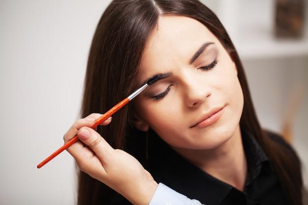 Jolie fille utilise les services d'une maquilleuse professionnelle dans un studio de beauté