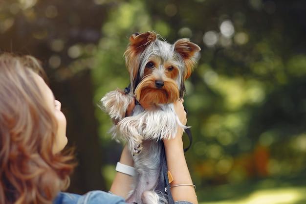 Jolie fille en veste bleue jouant avec petit chien