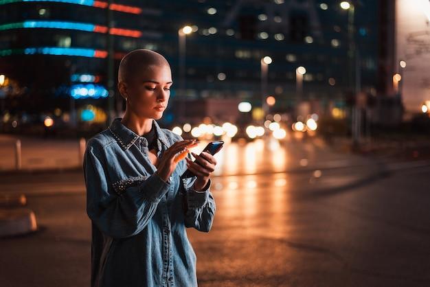 Jolie fille avec des vêtements élégants tenant le smartphone à l'extérieur le soir, ville illuminée